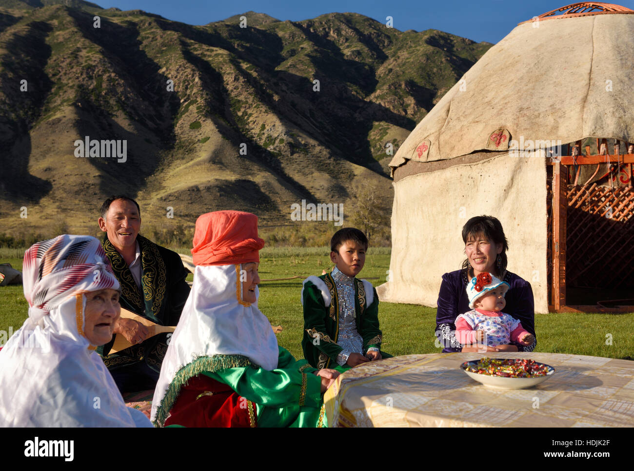 Family singing outdoors with Yurt under construction and Kungey Alatau mountain on the Chilik river Saty Kazakhstan - Stock Image