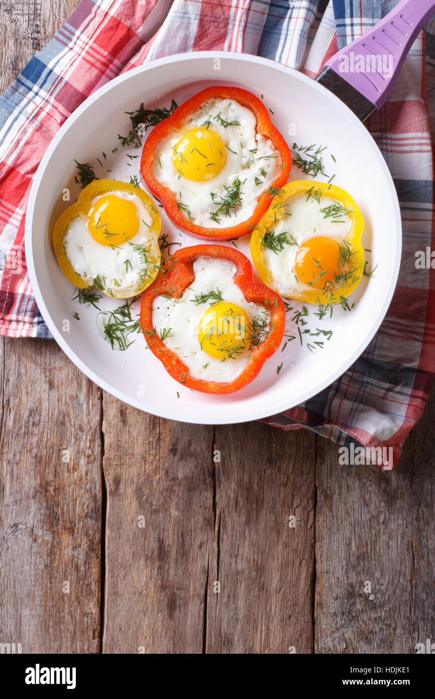 fried eggs with yellow and red peppers in a pan. vertical view from above - Stock Image