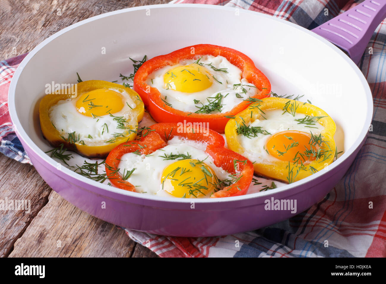 fried eggs with yellow and red peppers in a pan close-up. horizontal - Stock Image