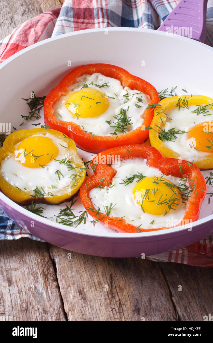 fried eggs with yellow and red peppers in a pan close-up. vertical - Stock Image