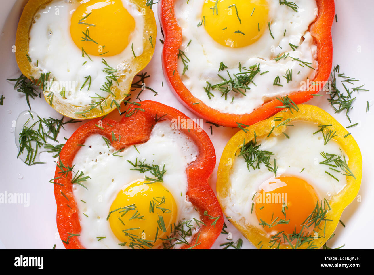 fried eggs with yellow and red peppers macro. horizontal view from above - Stock Image