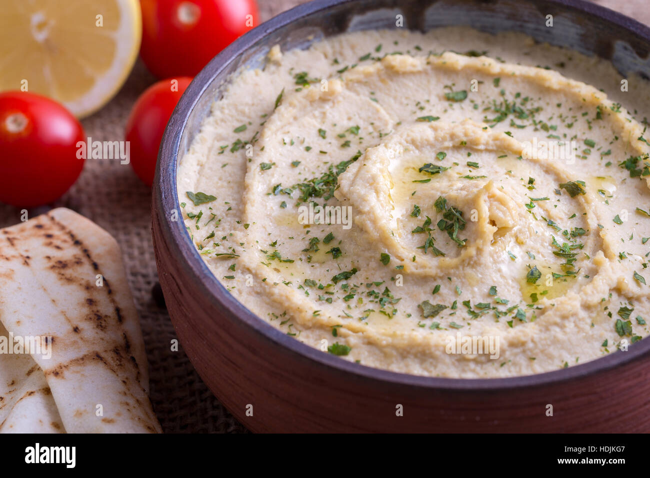 Humus in homemade bowl and vegetable. - Stock Image