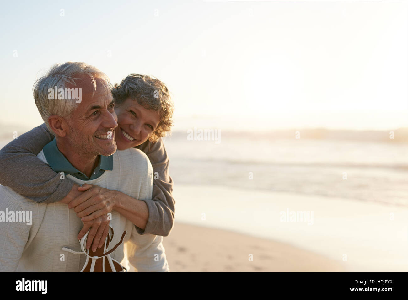 Portrait of happy mature man being embraced by his wife at the beach. Senior couple having fun at the sea shore. - Stock Image