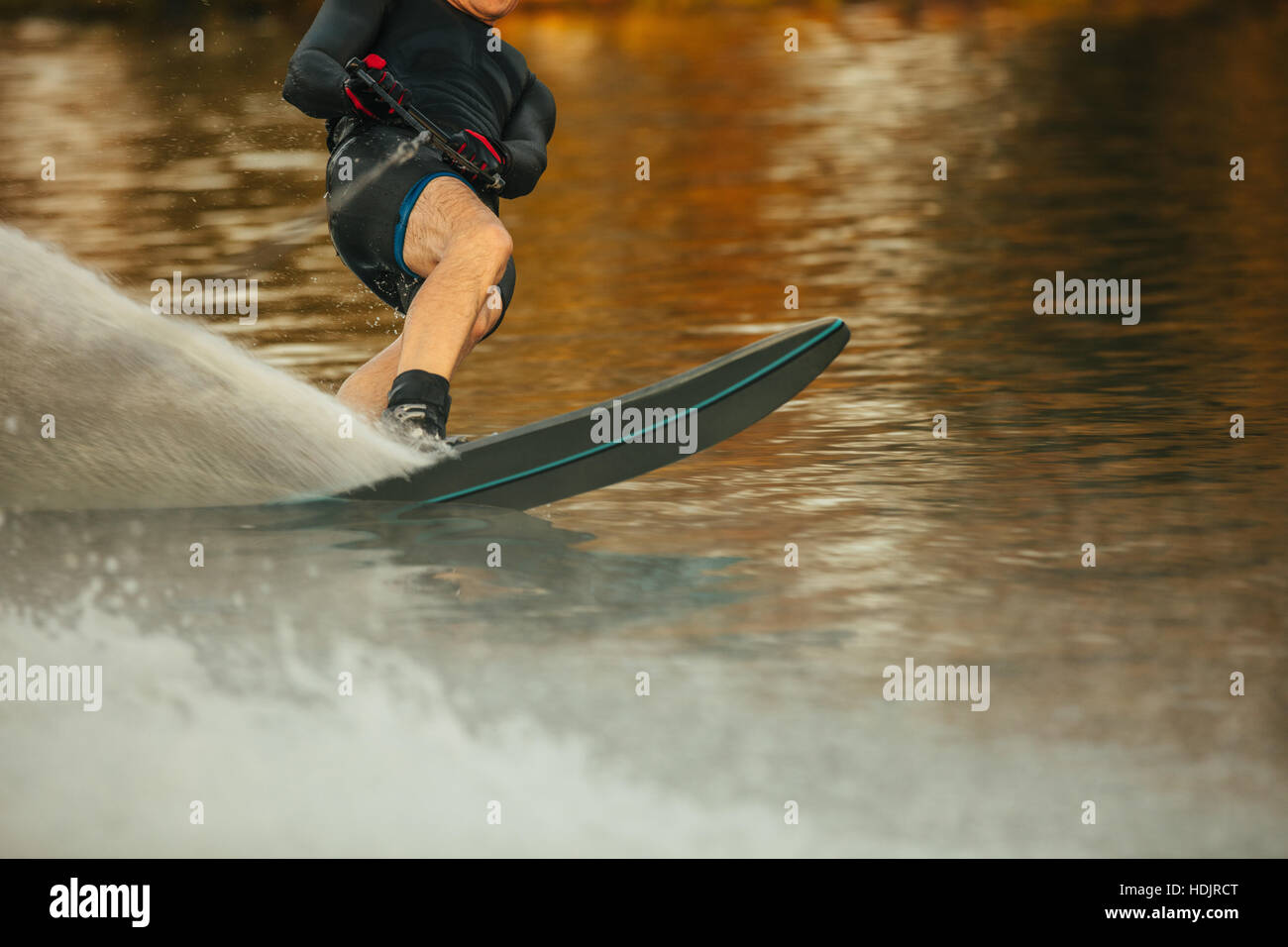 Man riding wakeboard on a lake. Male water skiing and surfing across the lake. - Stock Image
