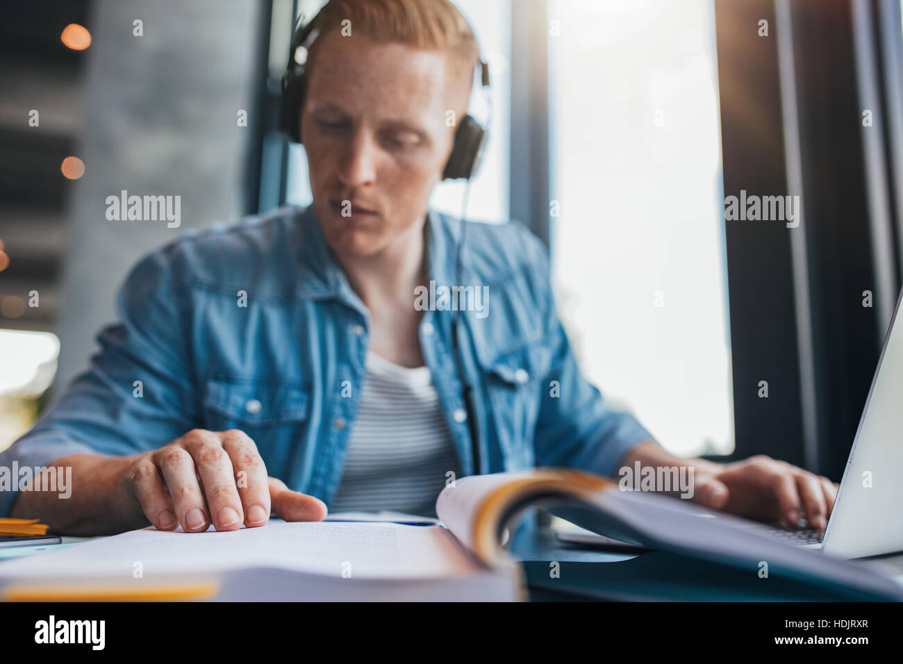 Young man sitting at table with books and laptop for finding information. Young male student studying in library - Stock Image