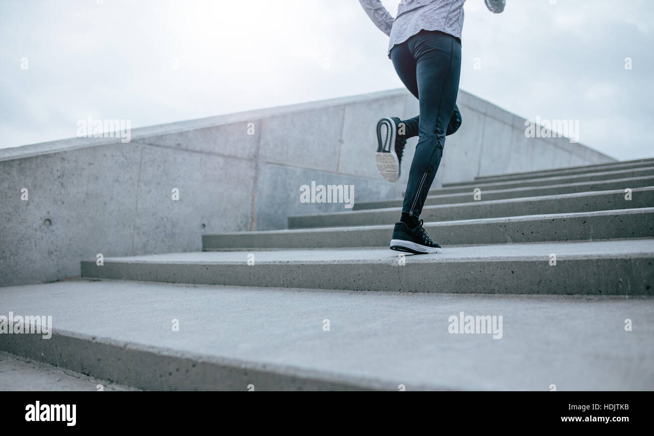 Low section shot of woman running up the stairs. Female legs climbing the steps in morning. Stock Photo