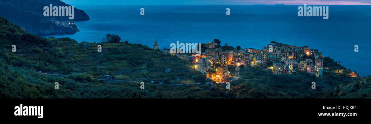 Twilight view over town of Corniglia with Manarola beyond, along the coast of Cinque Terre, Liguria, Italy Stock Photo