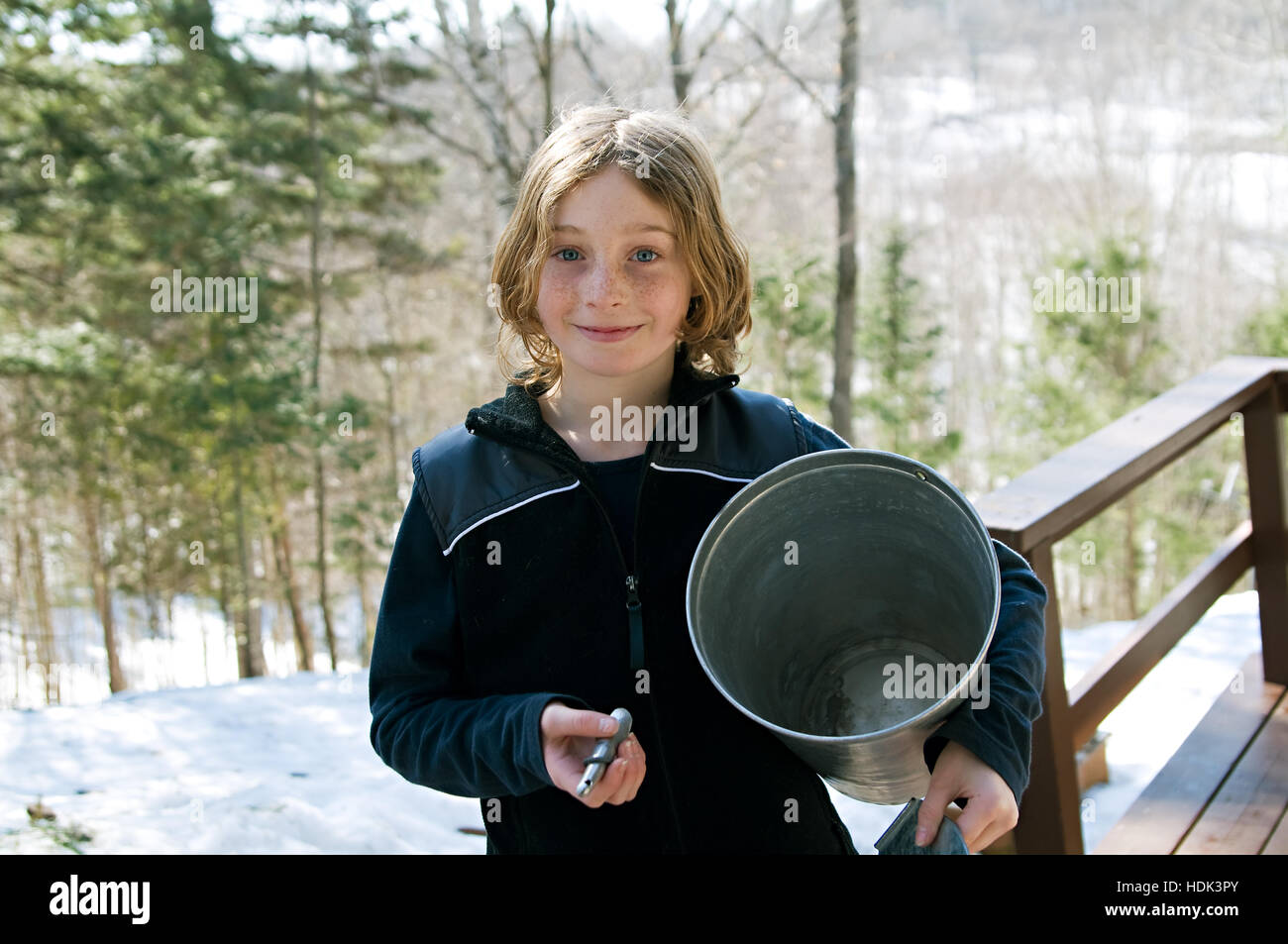 little girl holding a sap bucket and spigot to tap maple trees in the spring - Stock Image
