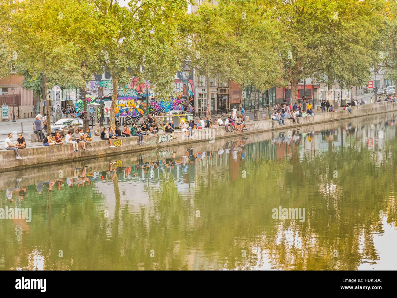 young people relaxing at canal saint-martin, quai de valmy - Stock Image