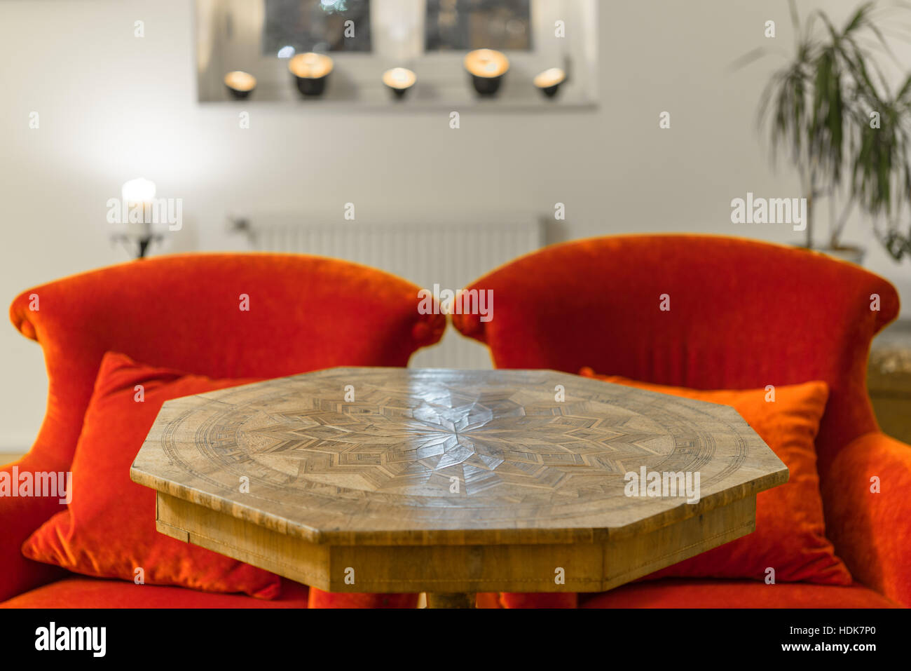 Antique side table with intarsia and red chair - Stock Image