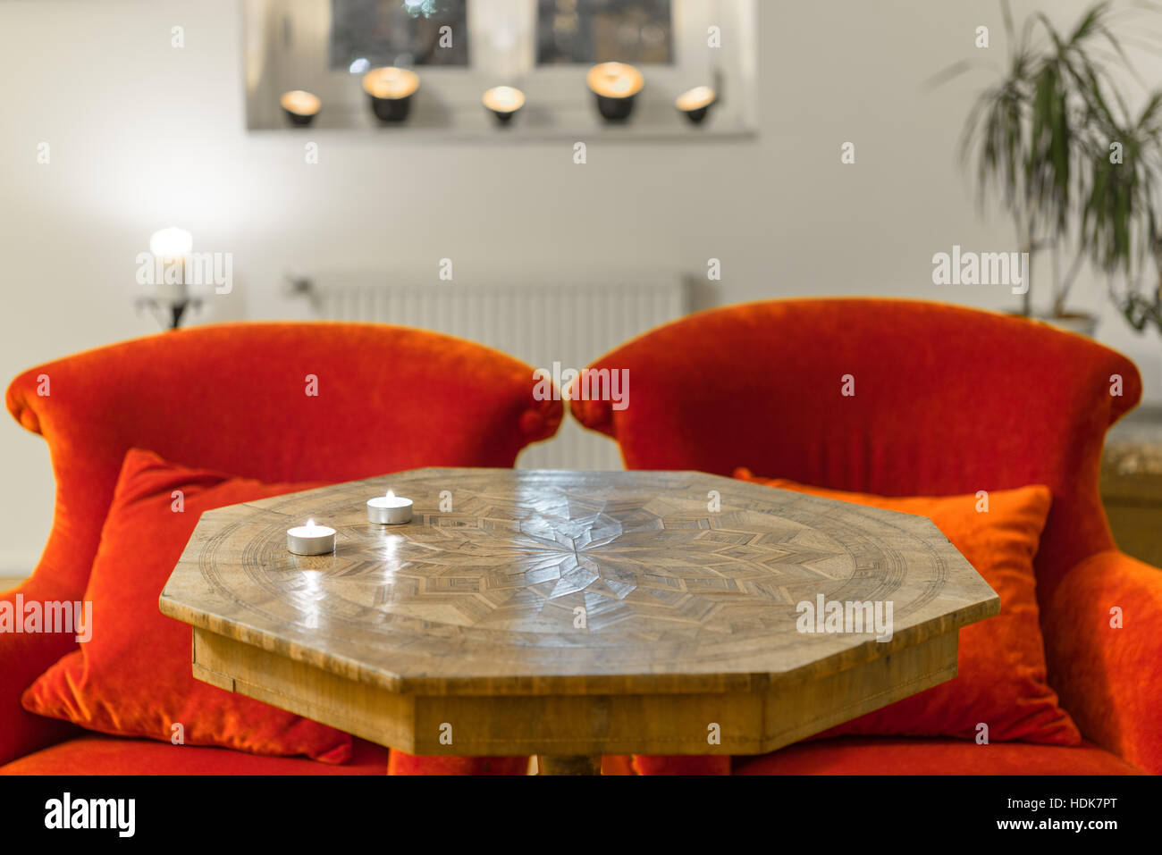 Candles on a antique side table with intarsia and red chair - Stock Image