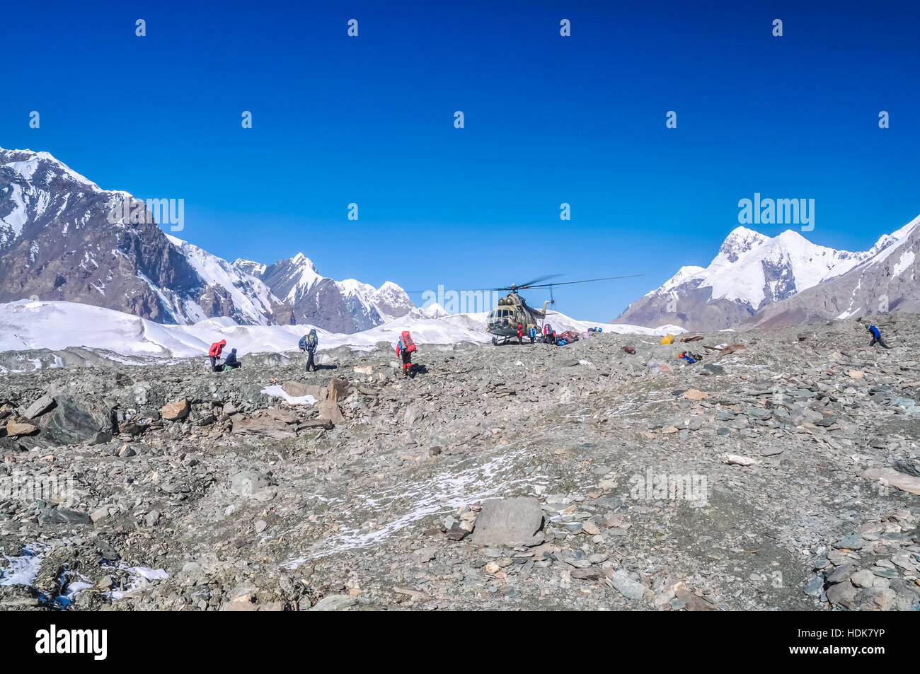 Photo of helicopter and hikers on rocky terrain surrounded by mountains near South Inylcheck Glaciar in Kyrgystan. - Stock Image