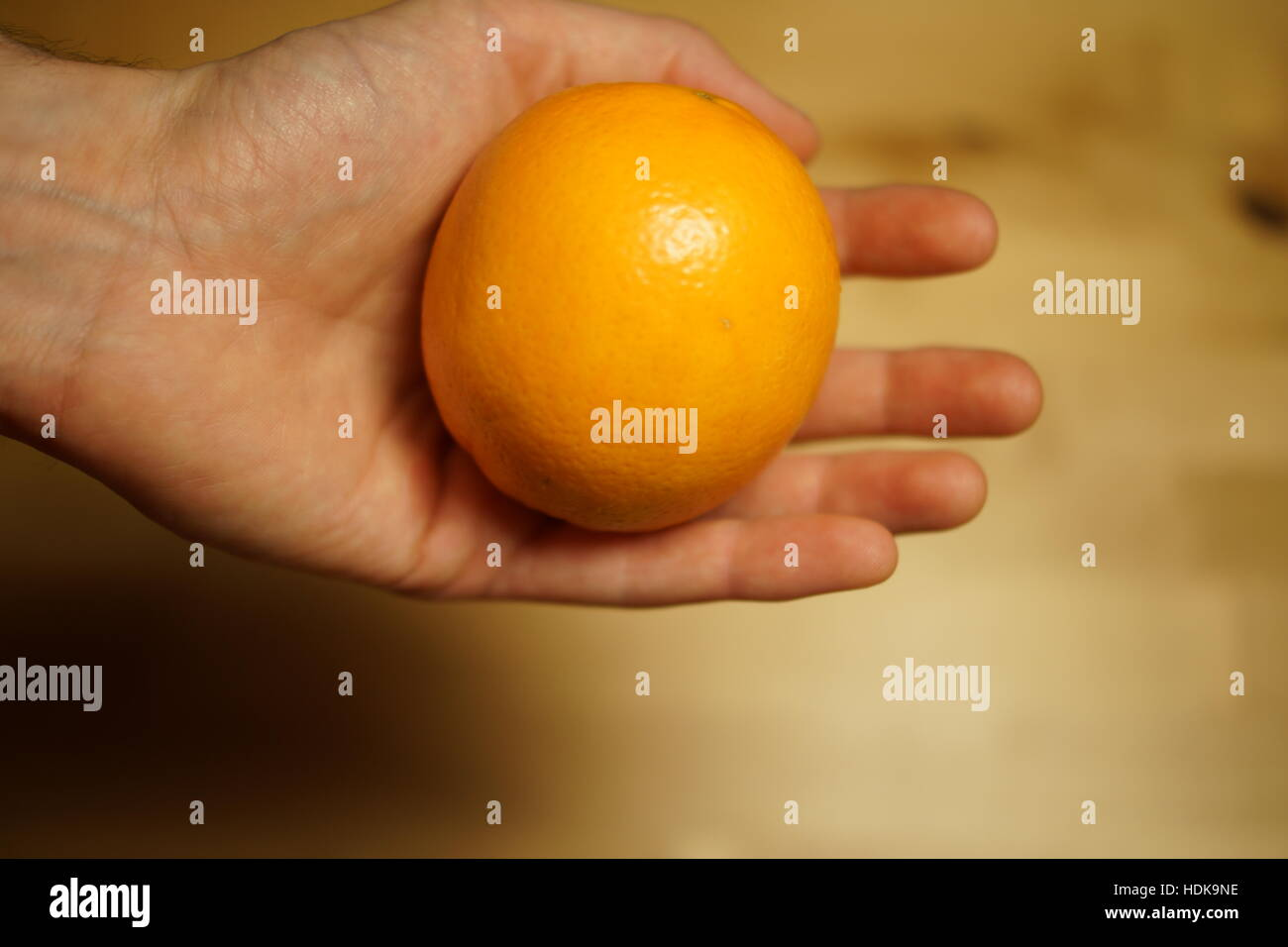 Orange in a hand - Stock Image