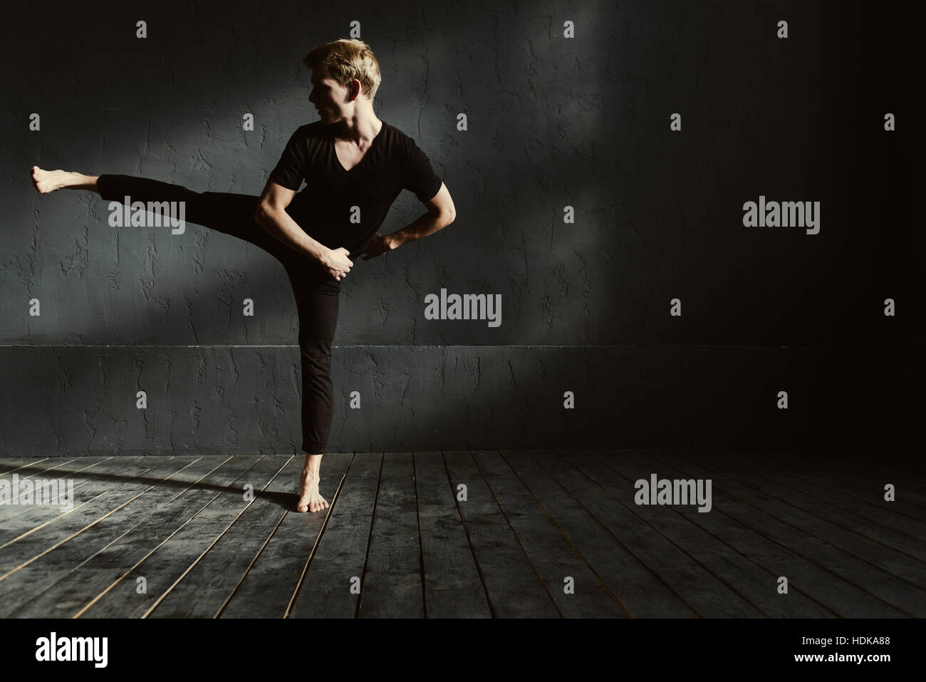 Trained young man dancing in the dark lighted room - Stock Image