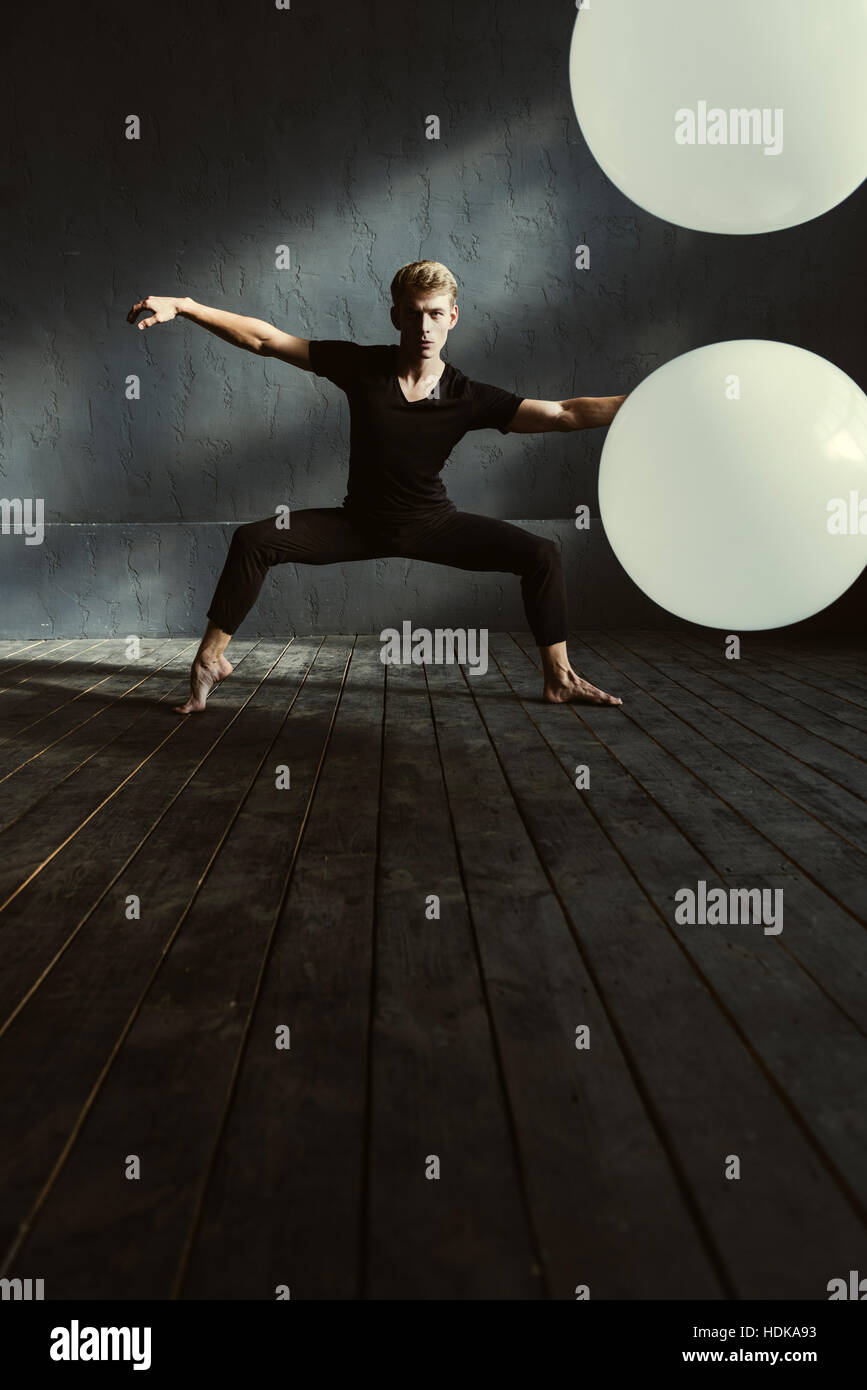 Young dancer training in the dark lighted room - Stock Image