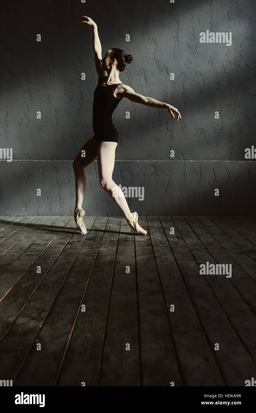 Young female dancer performing in the dark lighted room - Stock Image