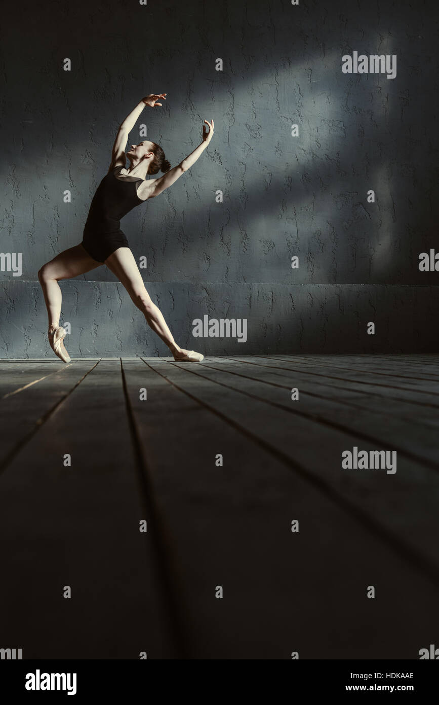 Charismatic young ballet dancer training in the black colored room - Stock Image