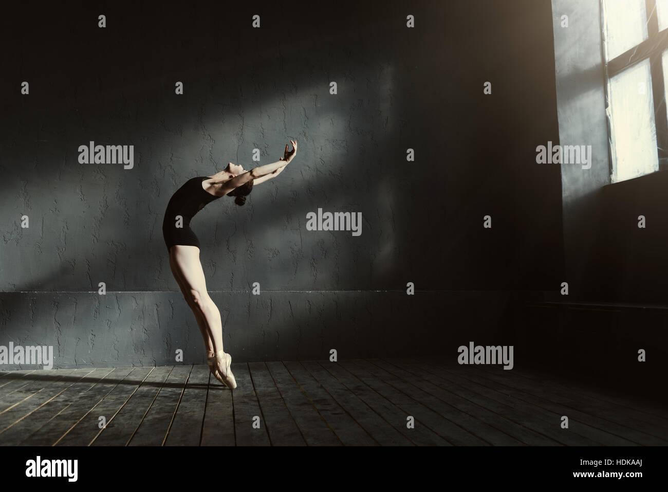 Flexible ballet dancer stretching in the dark lighted studio - Stock Image