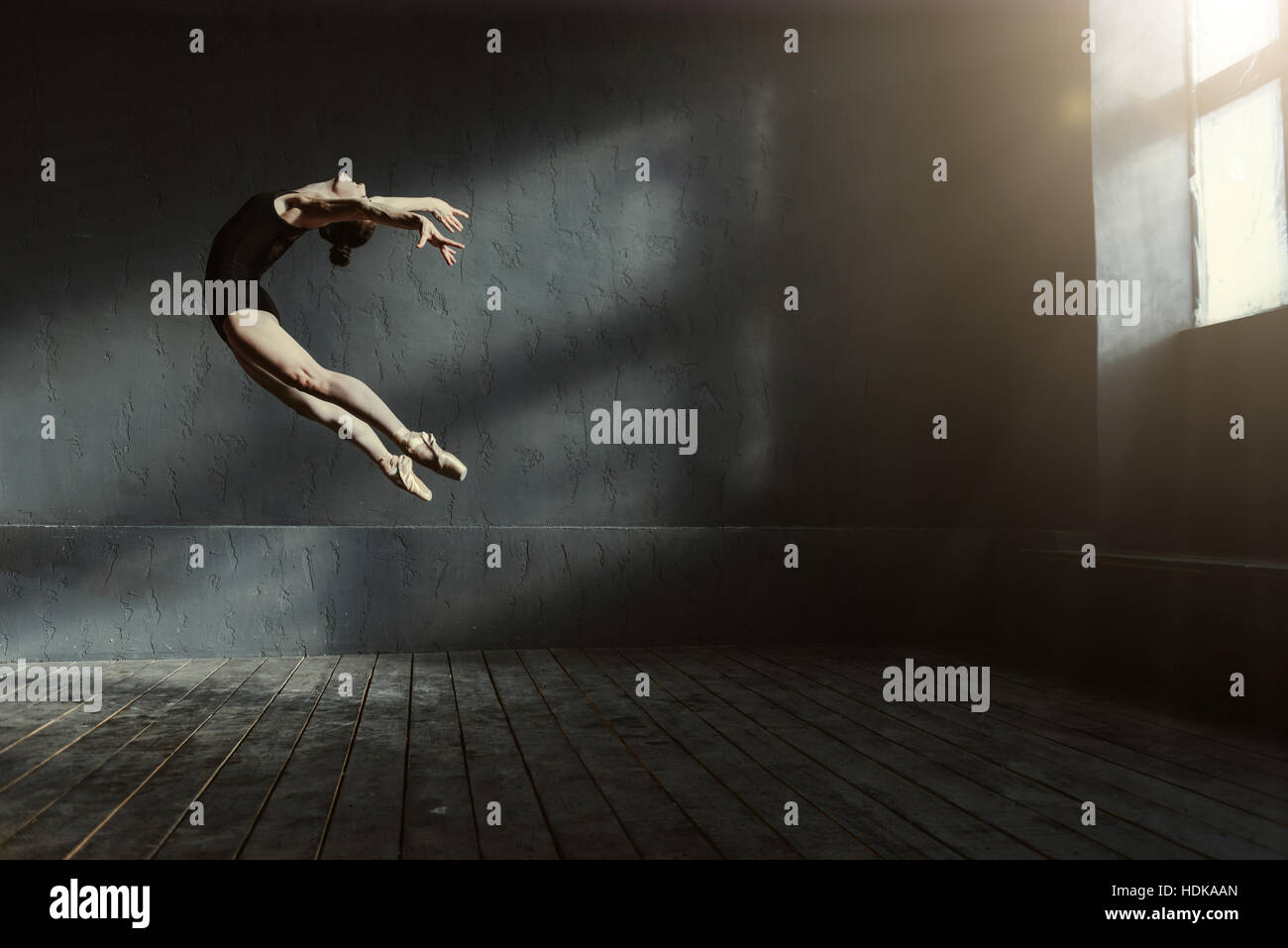 Professional ballet dancer performing in the dark lighted room - Stock Image