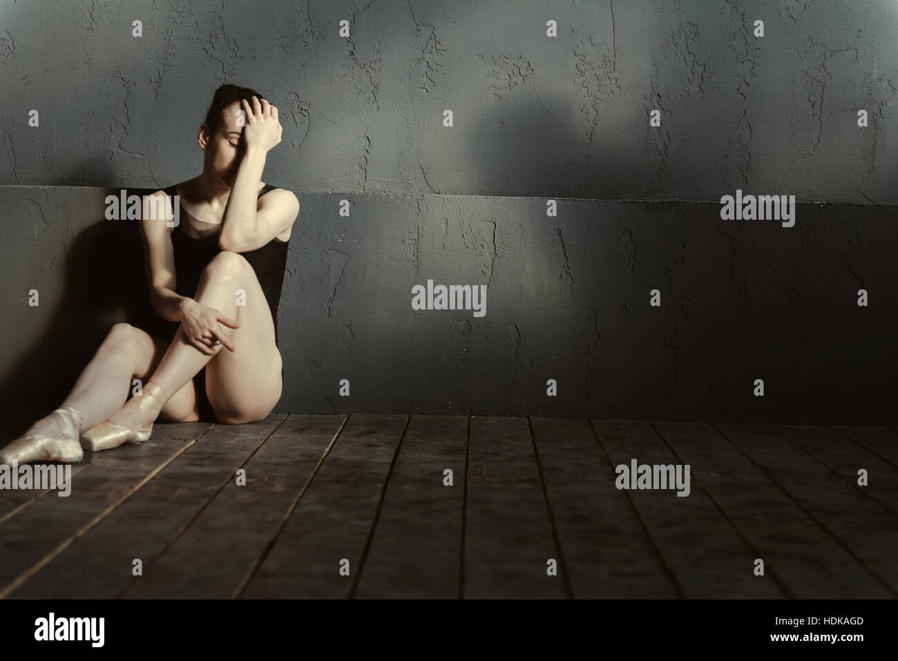 Disappointed ballet dancer sitting in the dark lighted room - Stock Image