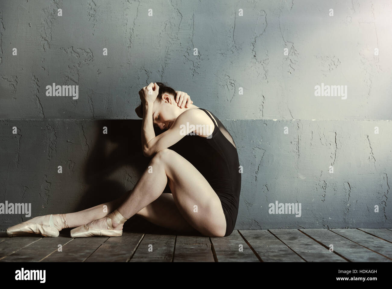 Exhausted ballet dancer crying in the dark lighted room - Stock Image