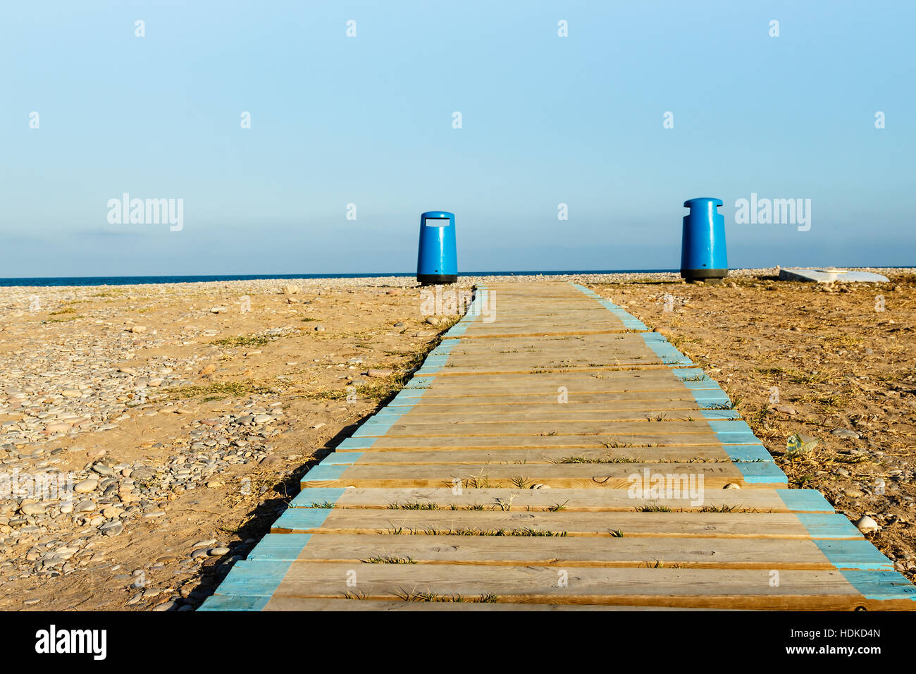 Wooden walkway on the beach with two litter bins in the background. Horizontal image - Stock Image