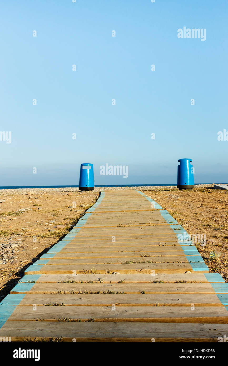 Wooden walkway on the beach with two litter bins in the background. Vertical image. - Stock Image