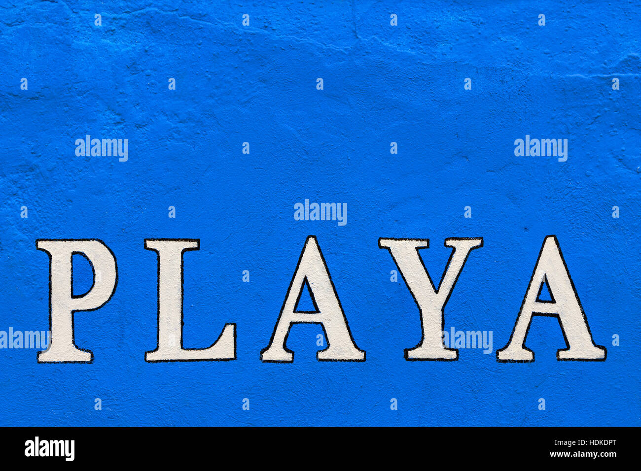 White 'playa' sign painted on a blue wall. Horizontal image. - Stock Image