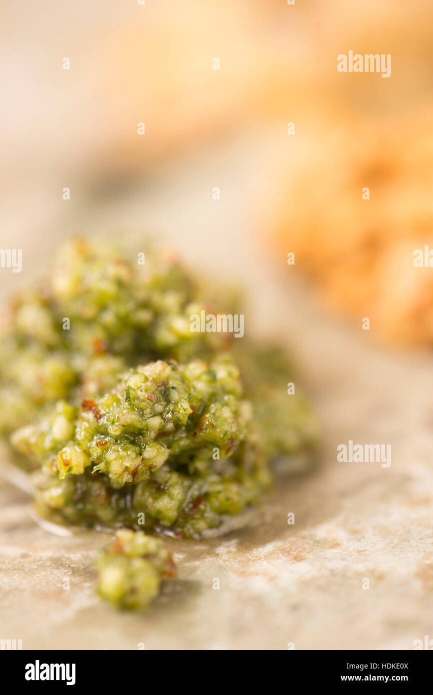 Green pesto sauce in extreme close up. Made of fresh basil. Traditional italian cuisine. - Stock Image