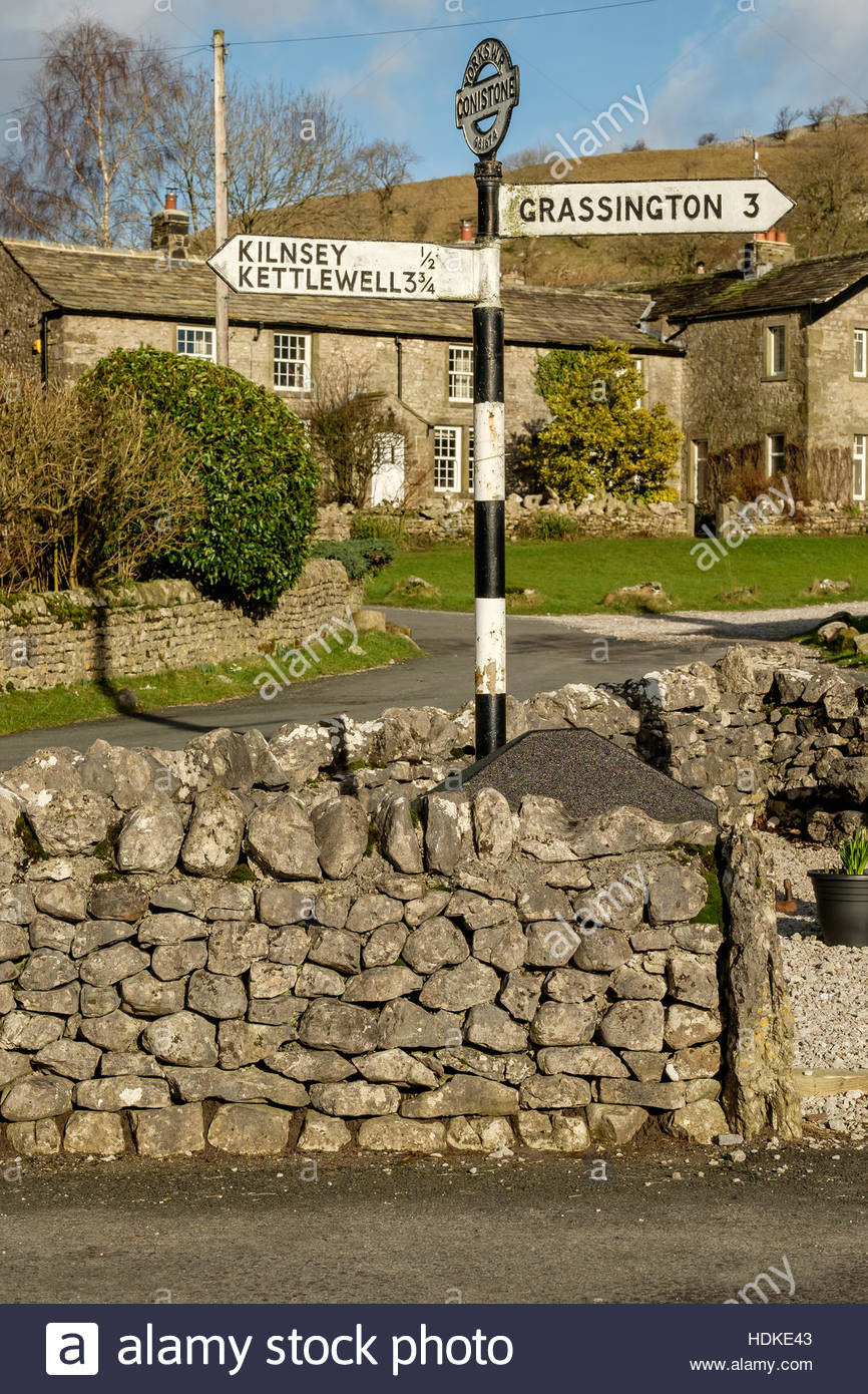 The centre of Conistone village in the Yorkshire Dales, North Yorkshire, England with an old metal signpost giving directions. Stock Photo