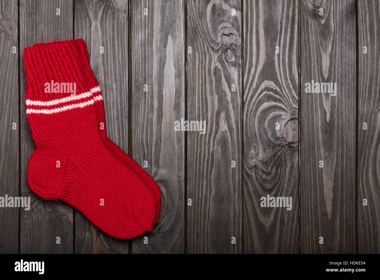 Knit red wool socks on dark wooden background. - Stock Image