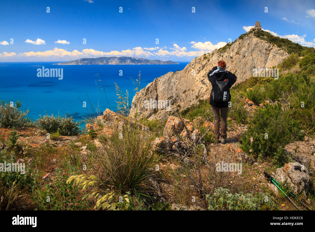 Monte Argentario, April 2016: Woman doing trekking and watching the Giglio island from Tuscan coast in a sunny day - Stock Image