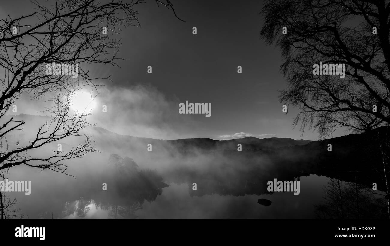 Sunrise morning mist loch black and white mystery - Stock Image