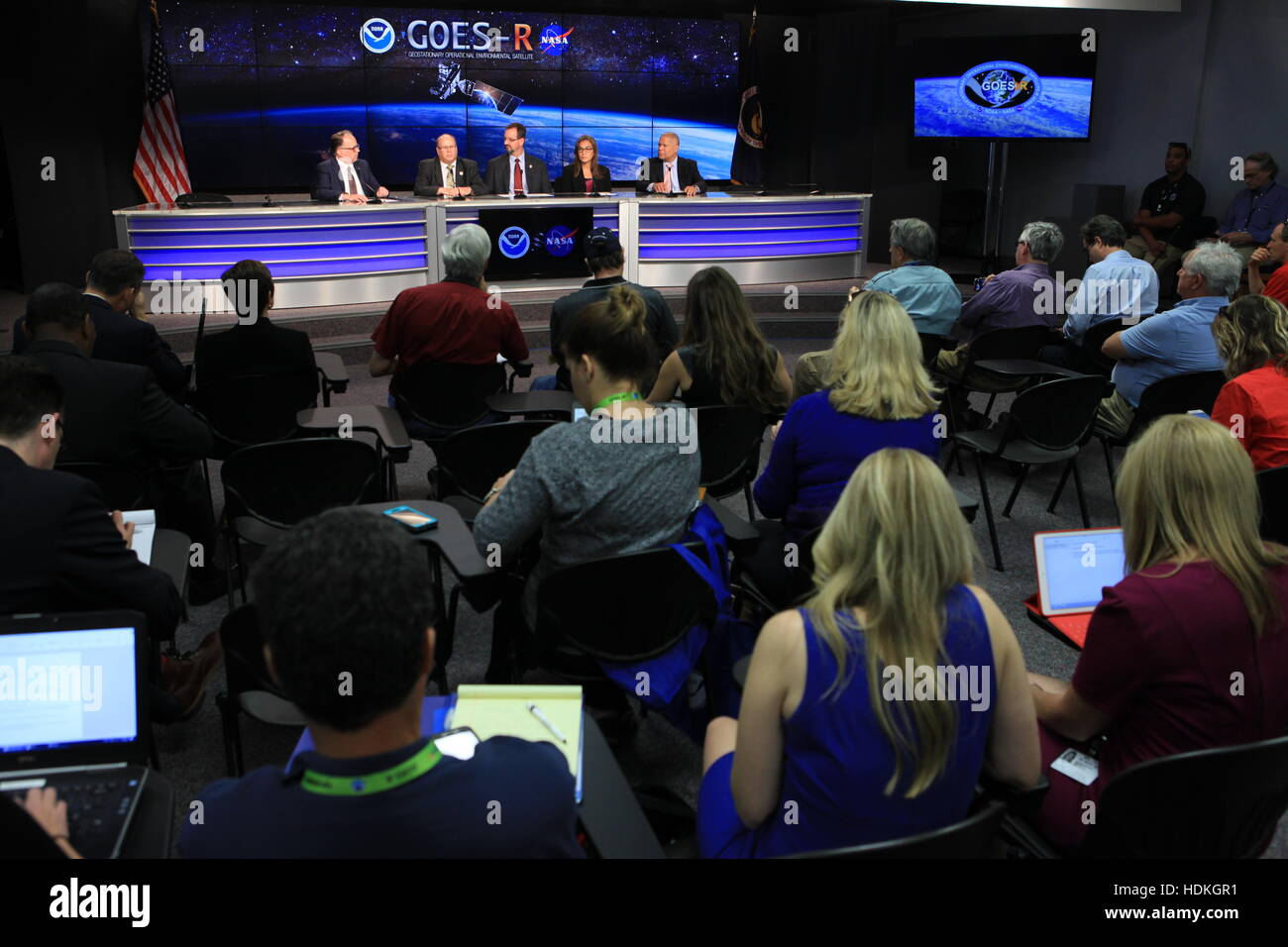 Members of the media watch a mission briefing on the NOAA Geostationary Operational Environmental Satellite (GOES - Stock Image