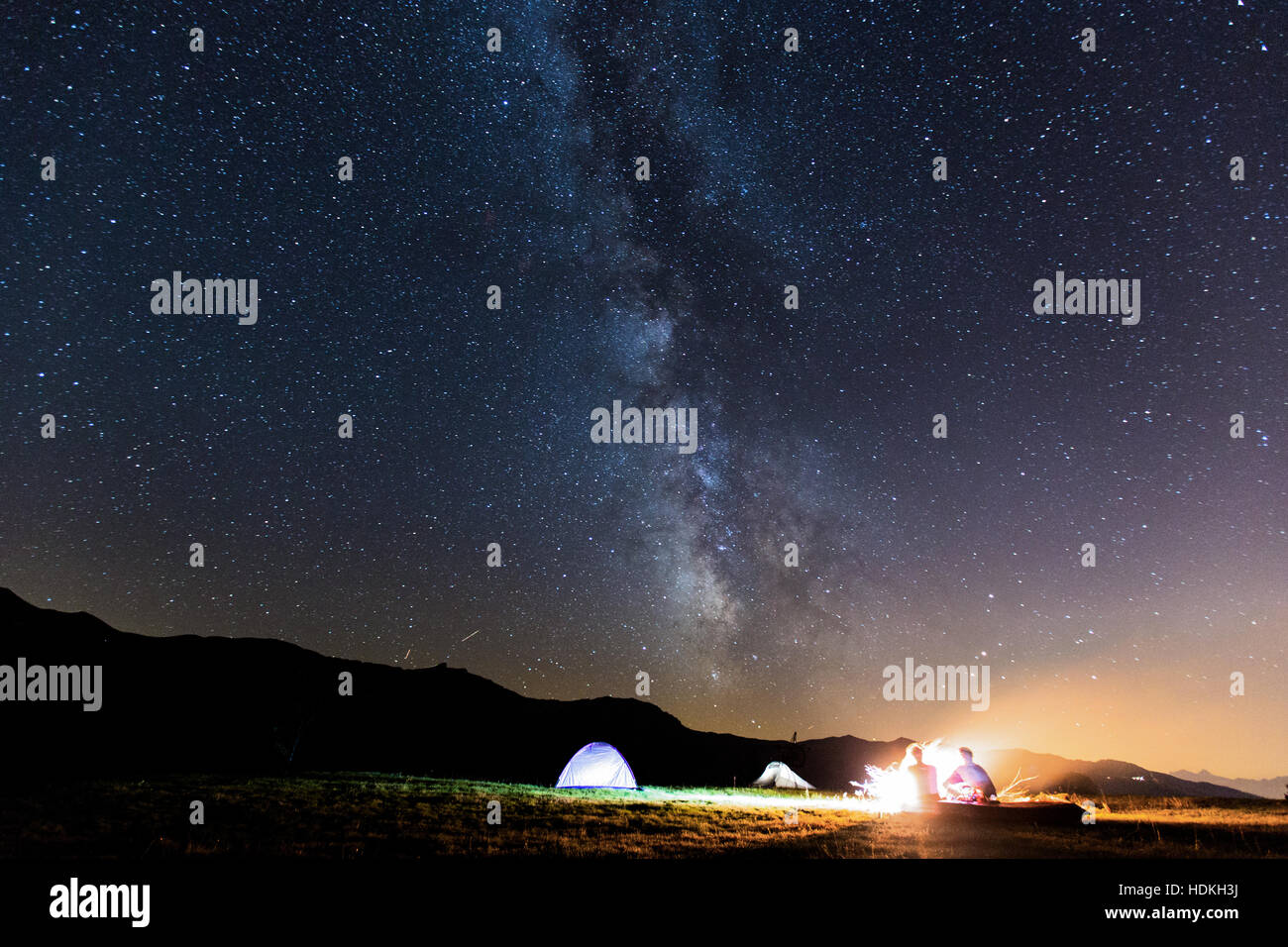 Milky Way. Night sky with stars and silhouette of two man around a fire - Stock Image