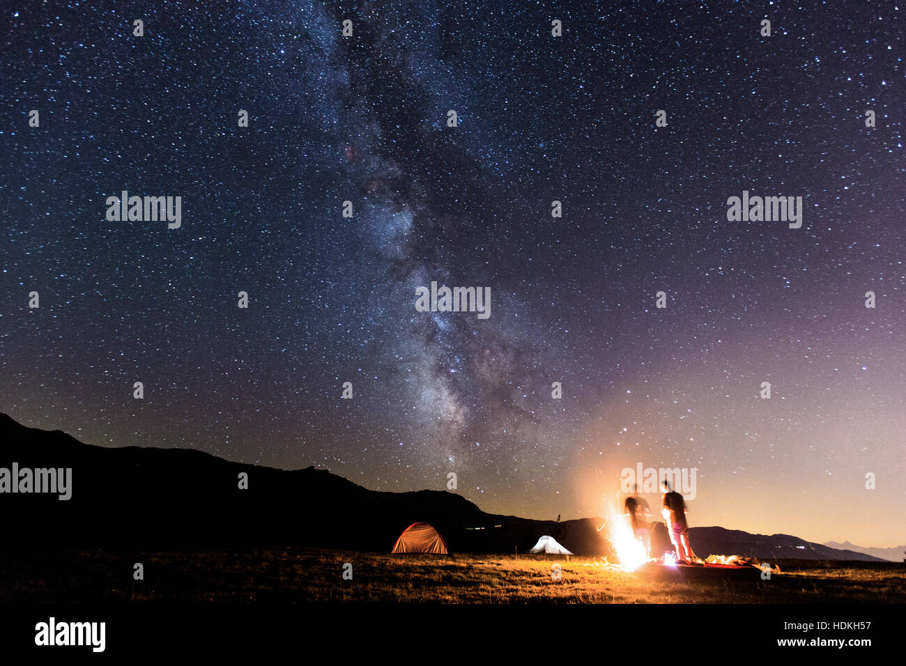 Milky Way. Night sky with stars and silhouette of two man around a fire Stock Photo