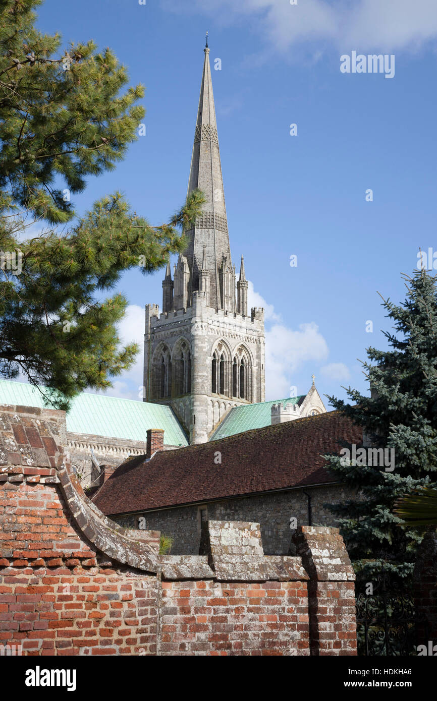 The spire of Chichester Cathedral stands against a blue sky as it rises over ancient brick walls. - Stock Image