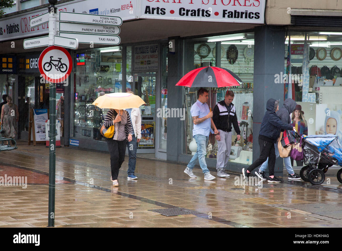 Pedestrians walk in a street in rainy weather. - Stock Image