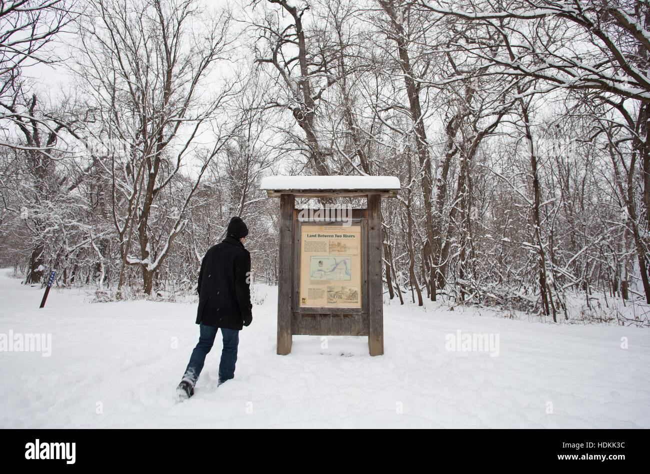A man walking through snow toward a sign with a map on Pike Island Fort Snelling State Park Trail Map on fort abercrombie state park map, three rivers park district map, fort snelling cemetery gravesite locator, saint anthony falls map, theodore wirth park map, fort griffin state park map, fort niagara state park map, fort snelling history, fort snelling minnesota map, inver grove heights map, lebanon hills regional park map, loring park map, fort snelling wedding reception, fort snelling buildings, fort snelling park fishing, fort snelling national cemetery flowers, big stone lake map, fort snelling hiking trail map, nickelodeon universe map, fort snelling national park,