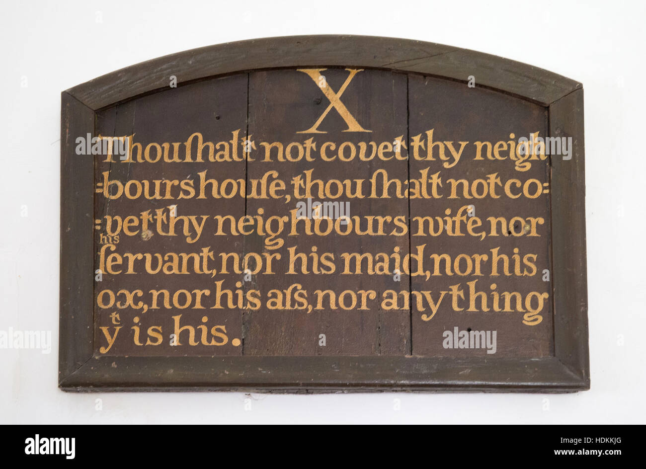 The tenth commandment - one of a series of ten framed pieces on the wall of an English country church in Devon - Stock Image