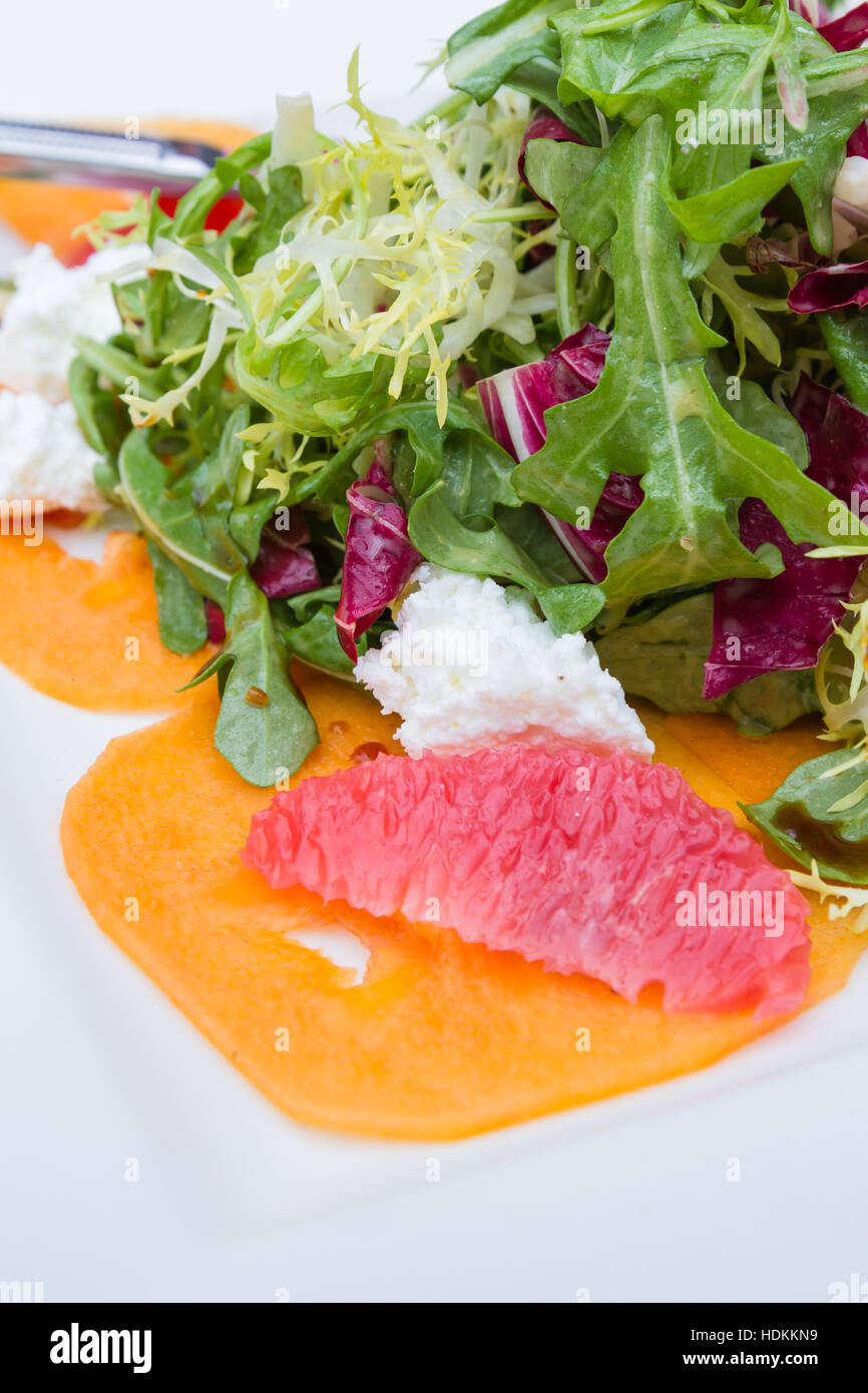 close up of a salad served with fruit and goat cheese with a variety of lettuces and a tangy dressing - Stock Image