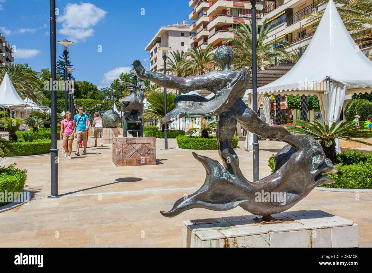 Spain, Andalusia, Province of Malaga, Costa del Sol, Marbella, Avenida del Mar, 'man above dolphin' bronze - Stock Image