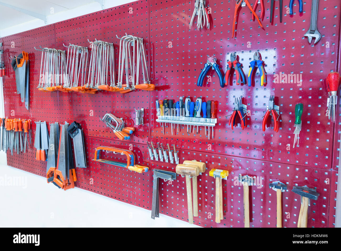 Many tools hanging at pegboard in classroom of school - Stock Image