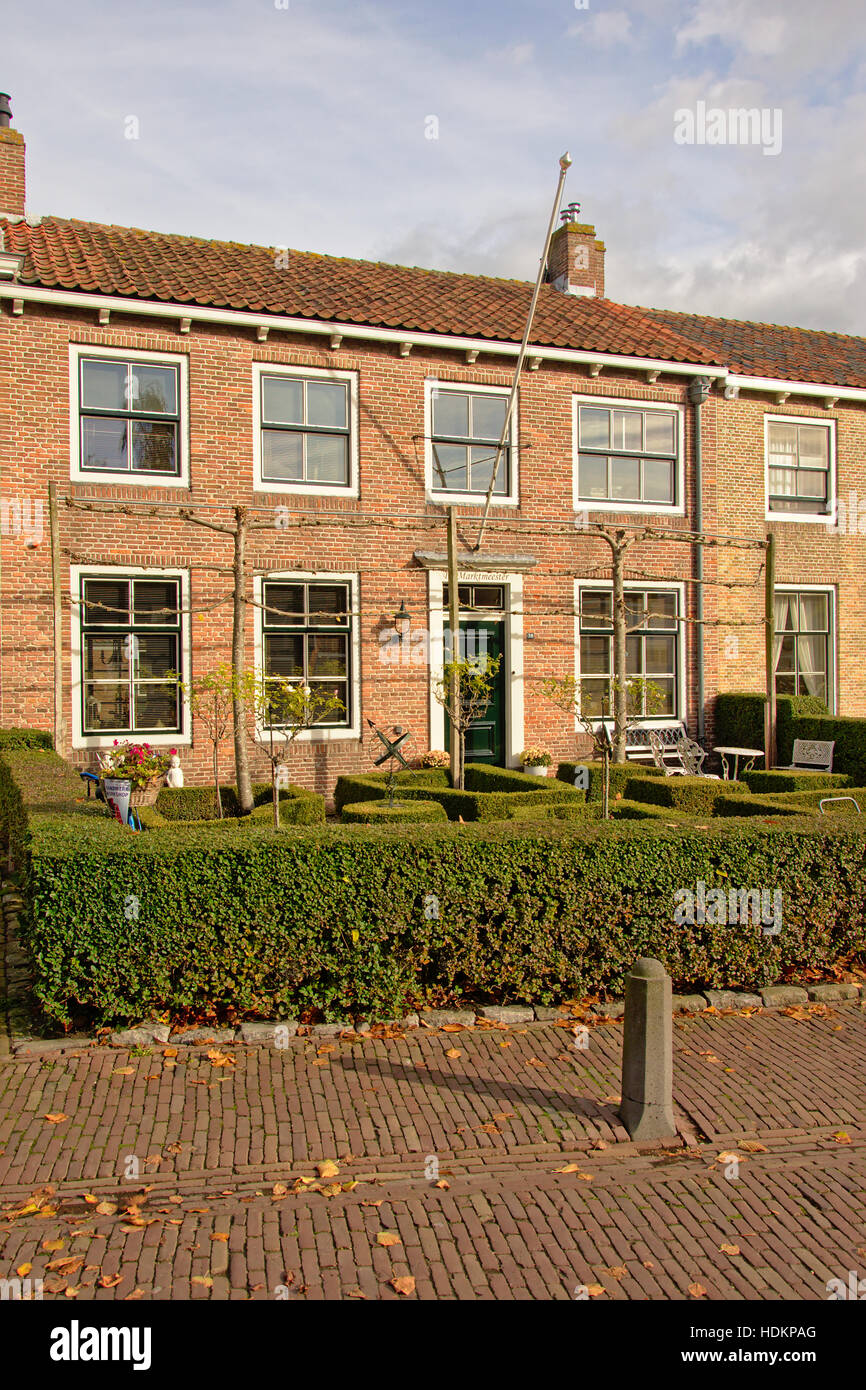 Cosy traditional brick stone housue with front garden with hedge in Veere, the Netherlands - Stock Image