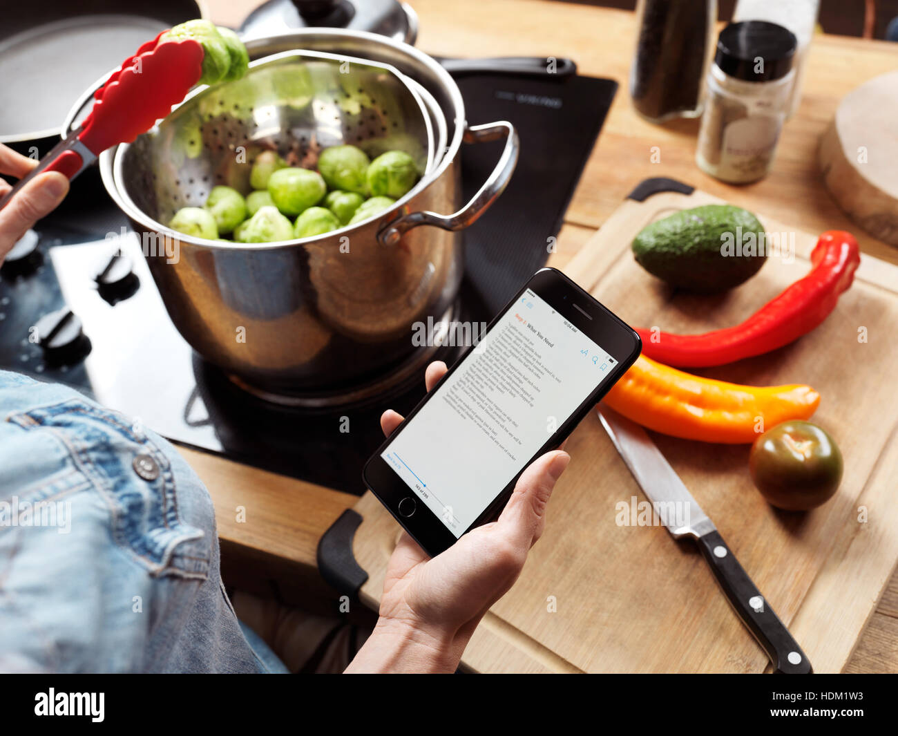 Woman cooking in the kitchen reading a recipe from iPhone 7 in her hand - Stock Image