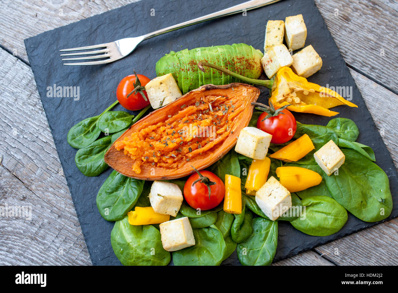 Salad with grilled vegetables: grilled sweet potatoes, tomatoes, avocados, spinach, tofu and pepper on dark slate Stock Photo