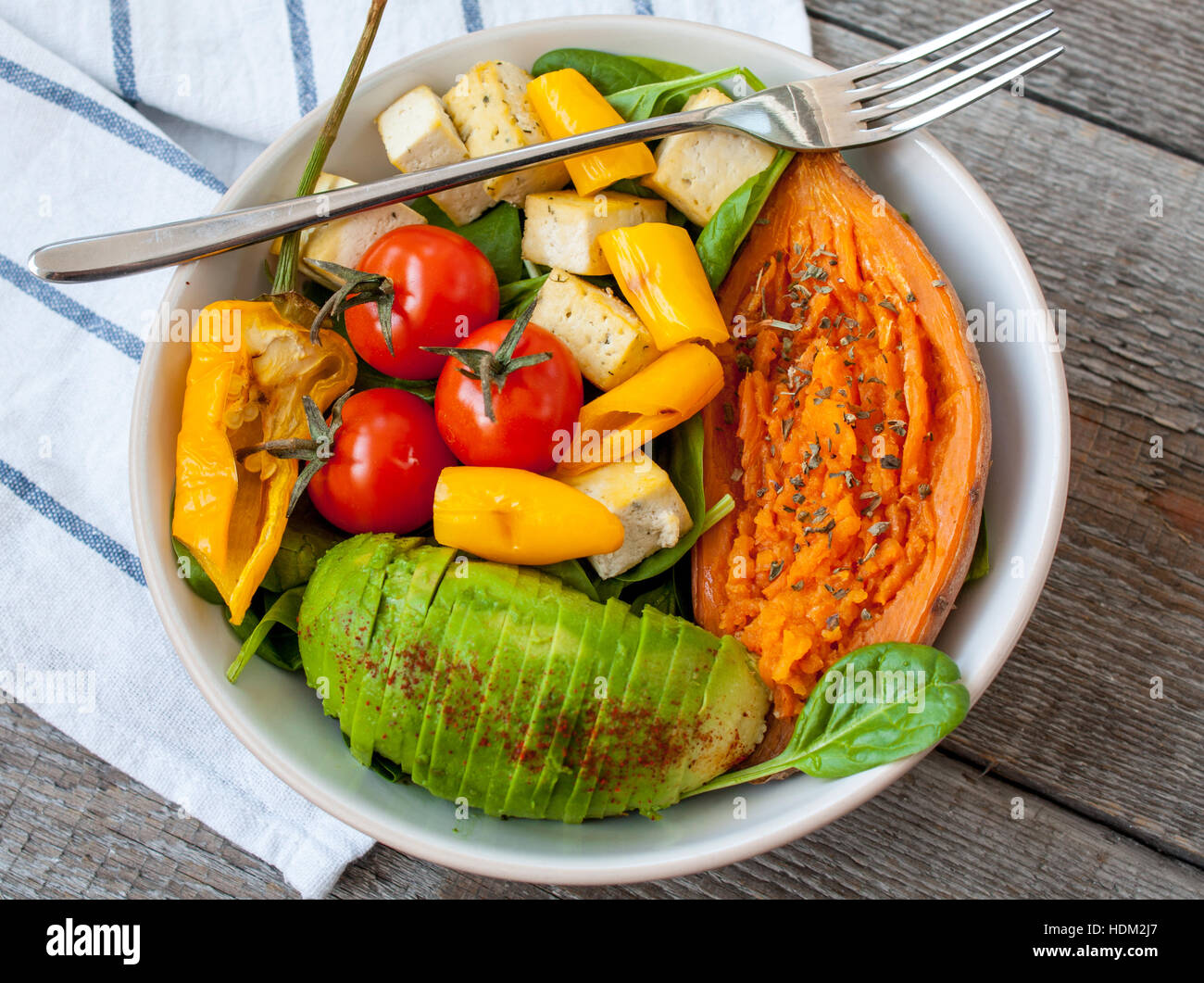 Salad with grilled vegetables: grilled sweet potatoes, tomatoes, avocados, spinach, tofu, pepper in a white bowl. Stock Photo