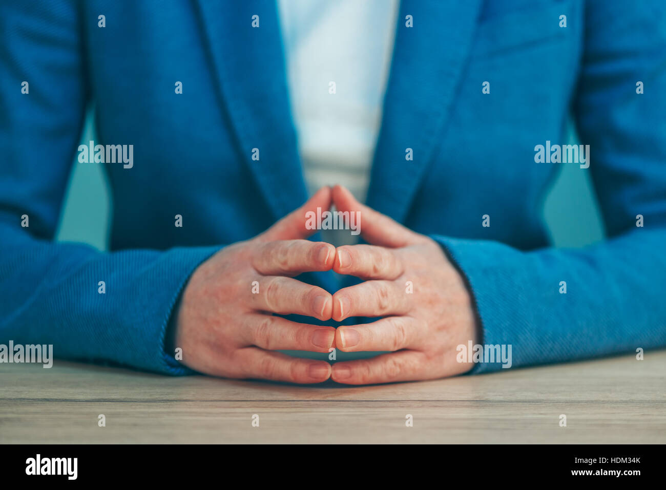 Businesswoman body language for confidence and self-esteem, hands with steepled fingers on office desk - Stock Image