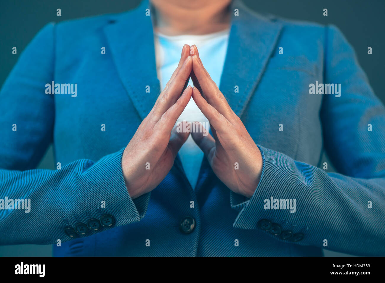 Businesswoman body language for confidence and self-esteem, hands with steepled fingers - Stock Image