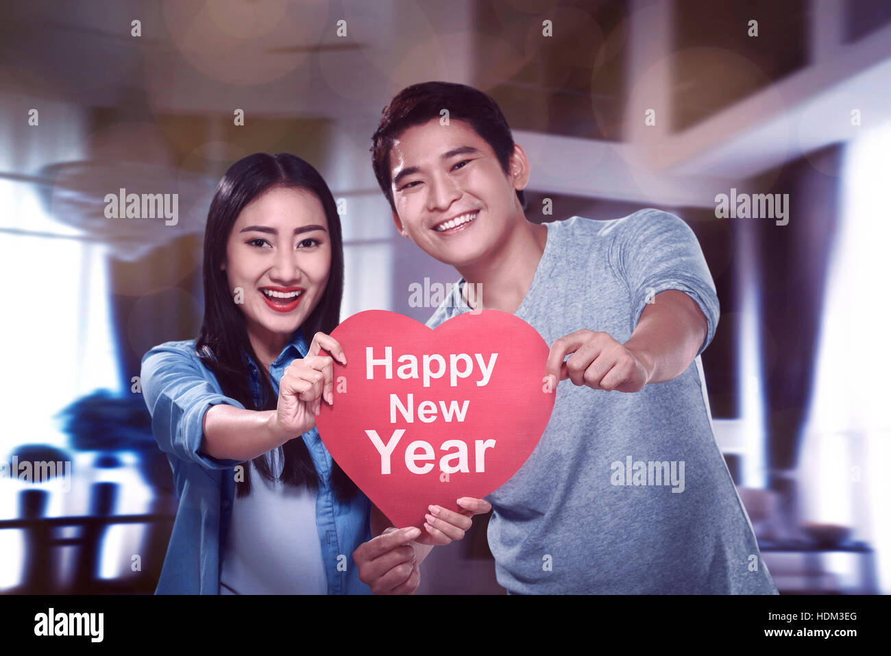 asian couple holding heart sign with happy new year typing